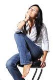 Attraktive Frau sitzt auf Stuhl Stockfotografie