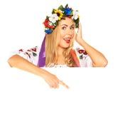 Attraktive Frau trägt ukrainisches Kleid hinter weißem Brett Lizenzfreie Stockfotos