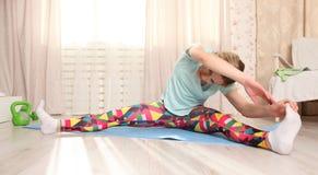 Attraktive Frau tun die Eignung, die zu Hause auf eine blaue Matte in der Wohnzimmermorgenzeit ausdehnt Stockbilder
