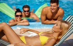 Attraktive Frau und Gesellschaft durch Pool Stockfotos