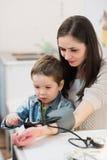 Attraktive Frau und ihr Kind mit einem Blutdruckmessgerät tonometer Lizenzfreies Stockfoto