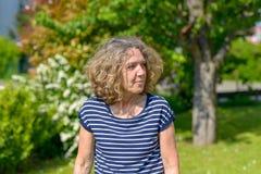 Attraktive Frau von mittlerem Alter, die in einen Garten geht lizenzfreie stockfotos