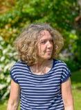 Attraktive Frau von mittlerem Alter, die in einen Garten geht lizenzfreie stockbilder