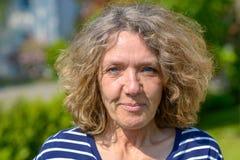 Attraktive Frau von mittlerem Alter in einem Garten lizenzfreies stockfoto