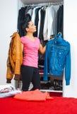 Attraktive Frau vor Wandschrank voll von Kleidung Stockfotografie
