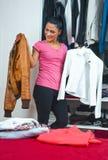Attraktive Frau vor Wandschrank voll von Kleidung Stockbild