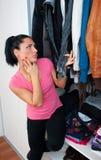 Attraktive Frau vor Wandschrank voll von Kleidung Stockfotos