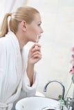 Attraktive Frau wäscht Gesicht mit Lotion Stockfotos