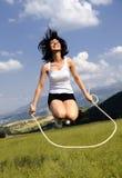 Attraktive Frauen des springenden Seils in der Wiese stockbild