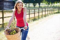 Attraktive Frauen-Reitfahrrad-Fahrt entlang Feldweg Lizenzfreie Stockbilder