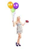 Attraktive Frauenholding Ballons und ein Geschenk Lizenzfreies Stockfoto