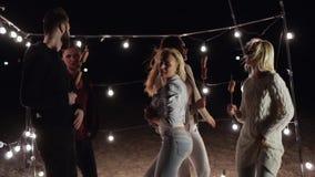 Attraktive Freunde, die zusammen am Sand auf Nachtstrand auf Hintergrund des Dekors mit Lampen tanzen stock video footage