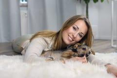 Attraktive freundliche Frau, die mit ihrem Hund streichelt Lizenzfreies Stockbild