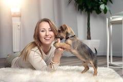 Attraktive freundliche Frau, die mit ihrem Hund streichelt Stockbild