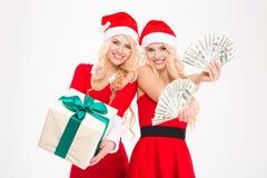 Attraktive frohe blonde Schwestern paart die Aufstellung mit Geld und Geschenk Lizenzfreie Stockfotografie