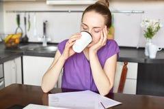 Attraktive Geschäftsfrau arbeitet mit den Dokumenten, gekleidet im zufälligen T-Shirt, heißer Kaffee der Getränke, hat Bruch, nac stockfoto
