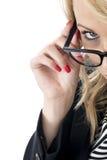 Attraktive Geschäftsfrau, die über Gläsern schaut Stockbild