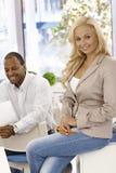 Attraktive Geschäftsfrau, die auf dem Schreibtischlächeln sitzt Lizenzfreie Stockfotos
