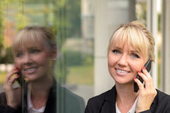 Attraktive Geschäftsfrau, die auf einem Mobile spricht Stockbild
