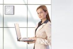 Attraktive Geschäftsfrau, die das Laptoplächeln verwendet lizenzfreie stockbilder
