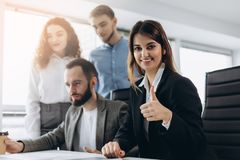 Attraktive Geschäftsfrau, die an der Kamera lächelt und Daumen oben während eines Geschäftstreffens zeigt stockbild