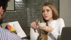 Attraktive Geschäftsfrau, die Diagramm mit ihrem Kollegen bespricht lizenzfreies stockbild