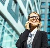 Attraktive Geschäftsfrau, die durch Telefon spricht Lizenzfreie Stockfotos