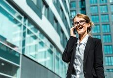 Attraktive Geschäftsfrau, die durch Telefon spricht Stockfotos