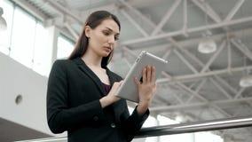 Attraktive Geschäftsfrau, die eine digitale Tablette bei der Stellung vor Fenstern in einer Bürogebäudeunterlassung verwendet stock video footage