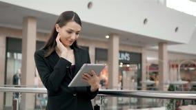 Attraktive Geschäftsfrau, die eine digitale Tablette bei der Stellung vor Fenstern in einer Bürogebäudeunterlassung verwendet stock footage