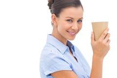 Attraktive Geschäftsfrau, die eine Kaffeetasse hält Lizenzfreies Stockfoto