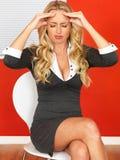 Attraktive Geschäftsfrau, die in einem Stuhl betont und mit Kopfschmerzen sitzt Lizenzfreie Stockbilder
