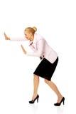 Attraktive Geschäftsfrau, die etwas drückt Stockfoto