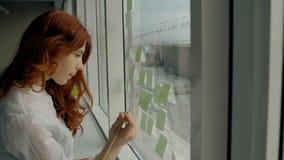 Attraktive Geschäftsfrau, die an Geschäftsstrategie auf Aufklebern auf dem Bürofenster arbeitet stock video footage