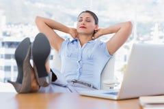 Attraktive Geschäftsfrau, die in ihrem Büro sich entspannt Stockfoto