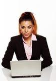 Attraktive Geschäftsfrau, die an ihrem Schreibtisch sitzt lizenzfreie stockfotografie