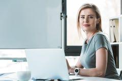 attraktive Geschäftsfrau, die Laptop und das Lächeln verwendet lizenzfreie stockfotos