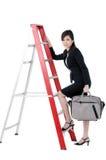 Attraktive Geschäftsfrau, die oben Strichleiter steigt Stockfotos
