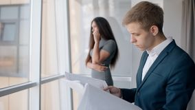 Attraktive Geschäftsfrau, die am Telefon, Geschäftsmann betrachtet das Projekt steht in der Firma spricht stock footage