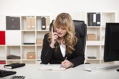 Attraktive Geschäftsfrau, die am Telefon plaudert Stockbild