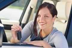 Attraktive Geschäftsfrau im neuen Auto, das Tasten zeigt Stockfotografie