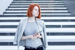Attraktive Geschäftsfrau mit einer Tablette in den Händen, die beiseite auf dem Hintergrund der Treppe im Geschäftszentrum schaue Stockfotografie