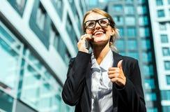 Attraktive Geschäftsfrau Talking telefonisch mit dem Daumen oben Stockbild