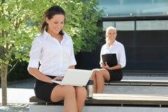 Attraktive Geschäftsleute mit Ordner und Laptop sitzendem outsid Lizenzfreie Stockfotos