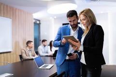 Attraktive Geschäftspaare unter Verwendung der Tablette in ihrer Firma stockfoto