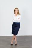 Attraktive Geschäftsfrau, die im Büro steht Stockbilder