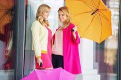 Attraktive girlfreinds, welche die Regenschirme tragen Stockbild