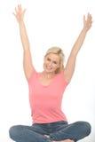 Attraktive glückliche erfreute junge Frau, die auf dem feiernden Boden sitzt Stockfoto