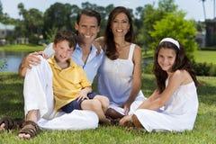 Attraktive glückliche Familie, die draußen sitzt Stockfoto