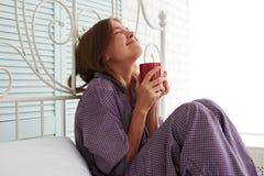 Attraktive glückliche Frau in den purpurroten Pyjamas, die am Kopfende sitzen stockfotografie